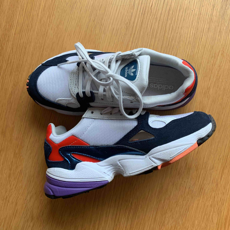 """Ett par Adidas i populära modellen """"Falcon"""". Använda några få gånger men ser ut som helt nya.  Färg: vit/blå med inslag av röd/lila . Skor."""