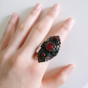 Vacker gothic ring med röda stenar! 🌹 Ringen är formad som ett kors med vackert mönster. Svårt att få den bra på bild då den är så mycket vackrare i verkligheten! fint skick och ringen är justerbar. Fri frakt 💌