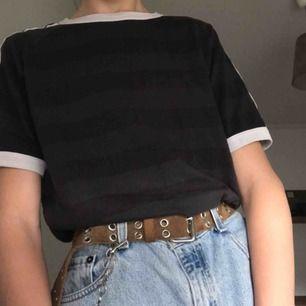 Så snygg vintage adidas t-shirt. Den är grå och svart randig med de tre strecken utöver armarna. Adidas trycket på bröstet är borttvättat.