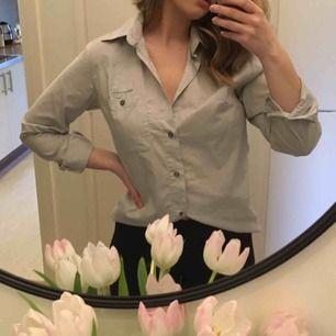 Ljusgrå skjorta! Bild 2 visar färgen bra. Den är rätt oversize (typ M/L) och jag har använt den till blåjeans eller off shoulder. 40kr frakt!
