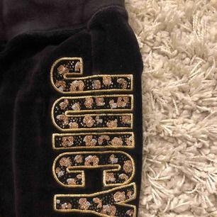 Svarta mjukisbyxor med gulddetaljer från Juicy Couture. Strl XS bootcutmodell. Byxorna har ett mindre hål på baksidan, men det går att enkelt åtgärda genom att sy/skräddare.
