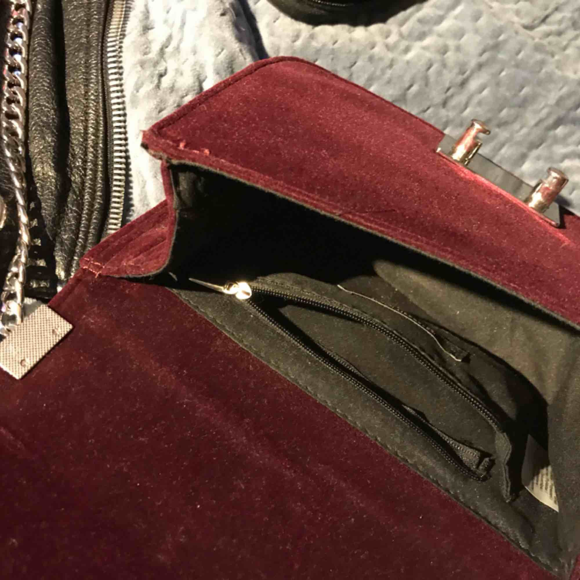 en fin liten väska i vinröd sammet köpt på gina tricot för nått år sedan! knappt använd, bra skick, perfekt storlek, axelbandet går att vika dubbelt som jag gjort på sista bilden för att göra den kortare men även längre!☺️. Väskor.