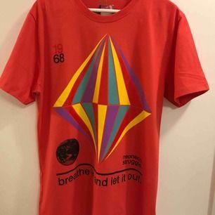 Röd T-shirt med snyggt grafiskt tryck. Storleken är en liten L, så skulle säga som en medium. Fler bilder och info, skicka ett pm. Ny och inte använd. Skickas mot porto 18:-