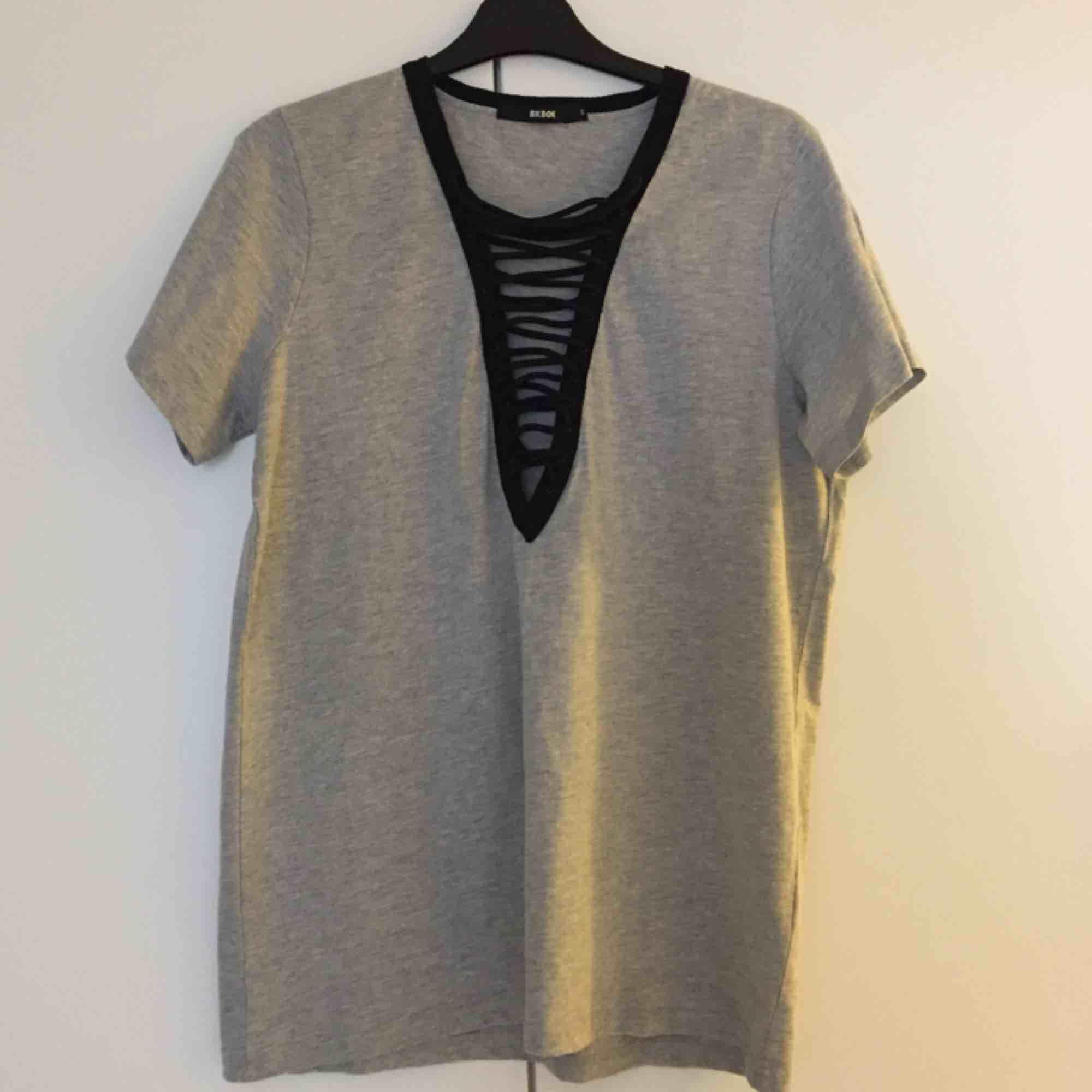 Snygg gråmelerad urringad oversize t-shirt med svarta snördetaljer från Bikbok. Aldrig använd, endast provad och tvättad. 📬 Frakt ingår i priset!. T-shirts.