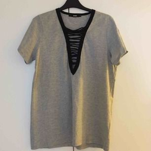 Snygg gråmelerad urringad oversize t-shirt med svarta snördetaljer från Bikbok. Aldrig använd, endast provad och tvättad. 📬 Frakt ingår i priset!