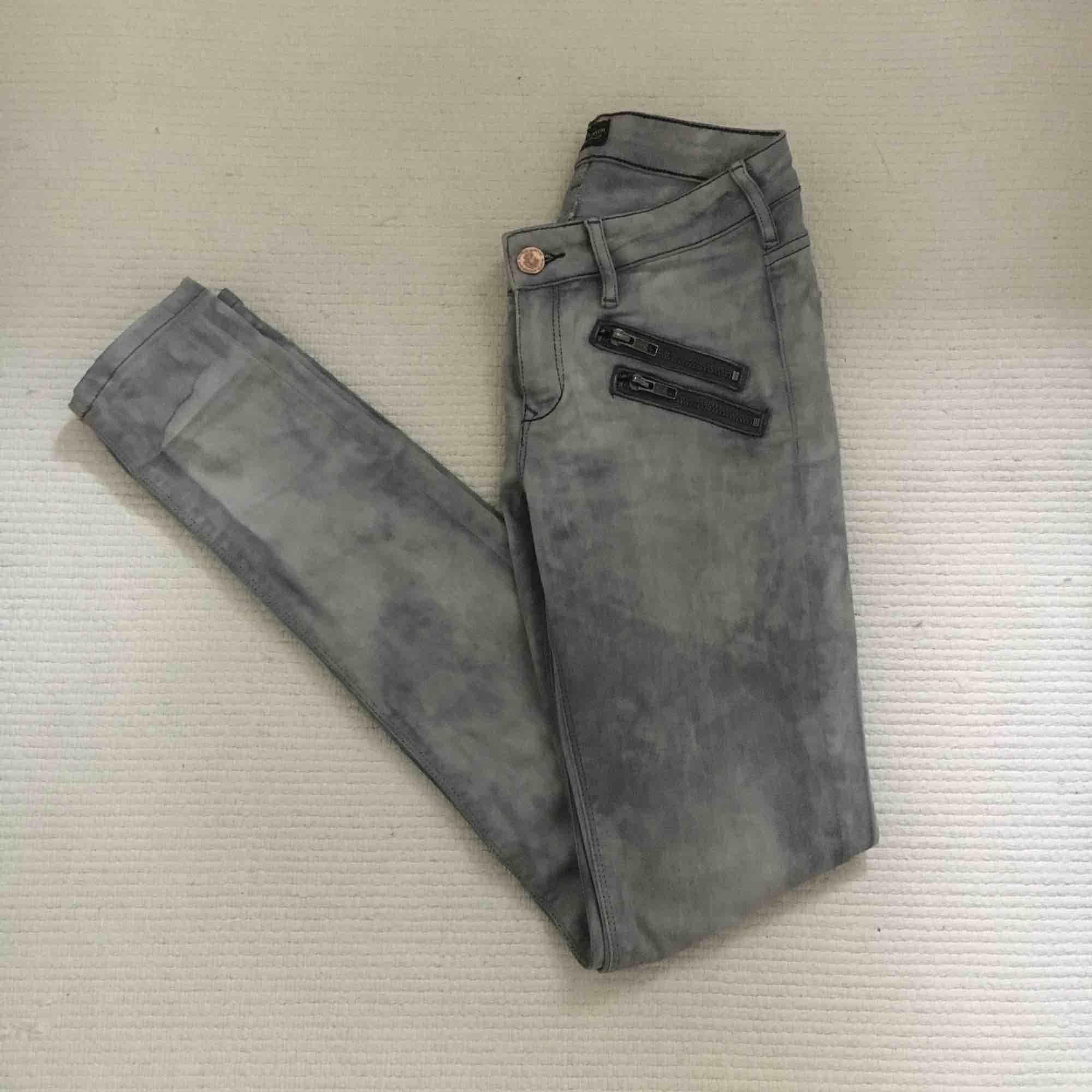 Jättecoola jeans i grå/acid wash med dragkedjedetaljer i fram. De är normalhöga i midjan och materialet är strechigt. Storlek W24 L32. Sparsamt använda, mycket fint skick! Jag bjuder på frakten!. Jeans & Byxor.