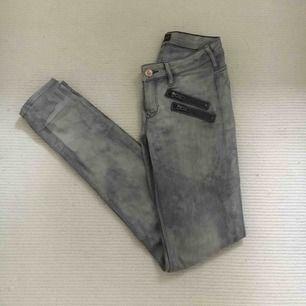 Jättecoola jeans i grå/acid wash med dragkedjedetaljer i fram. De är normalhöga i midjan och materialet är strechigt. Storlek W24 L32. Sparsamt använda, mycket fint skick! Köparen står för eventuell frakt.