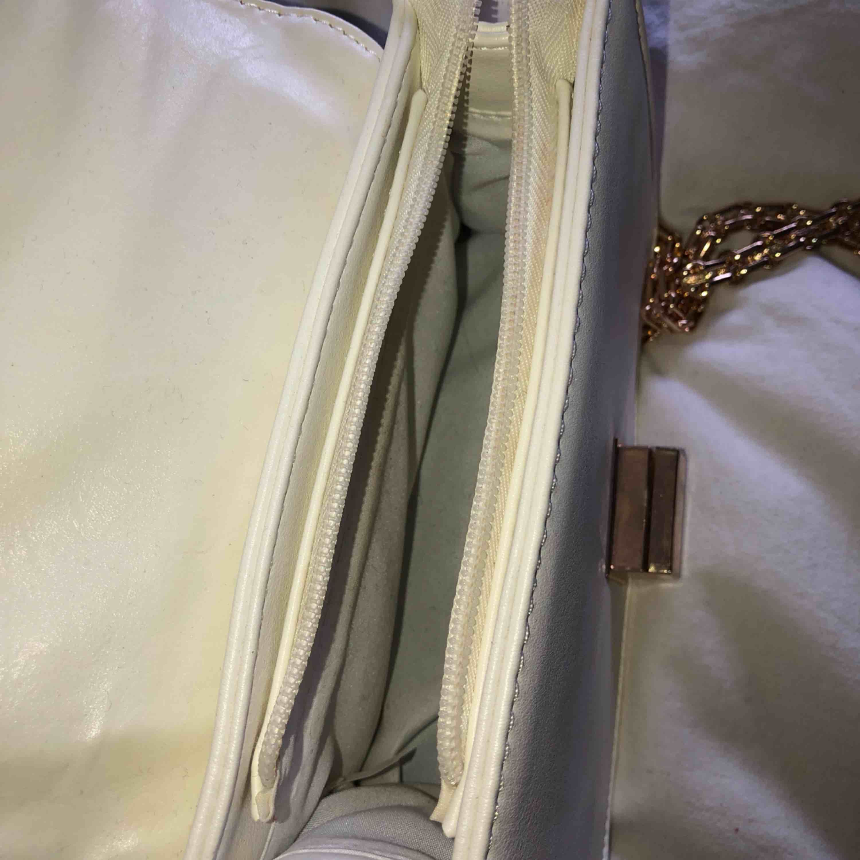 Vit väska, med gulddetaljer, använd 4-5 gånger, småmärken på låset annars är den bara i fint o rent skick.. Väskor.
