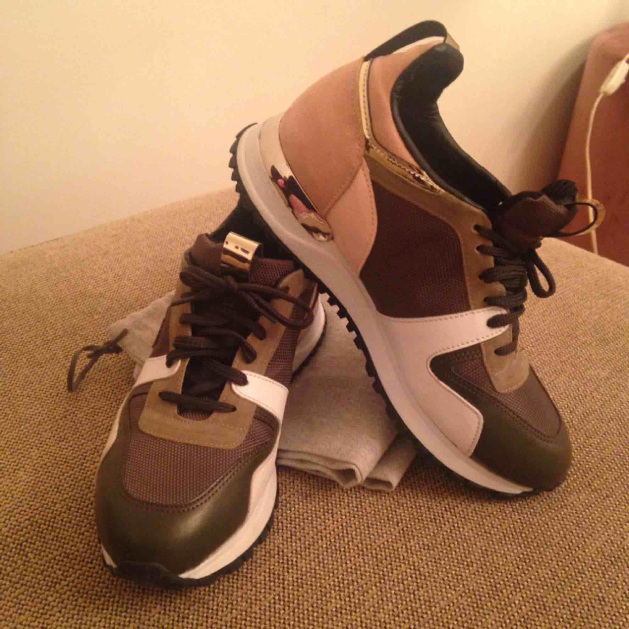 Sneakers från Louis Vuitton x SUPREME. Storlek 38. Färg: grön, rosa, silver och vit. Testade ute vid 1 tillfälle, kan tyvärr inte ha dom pga ryggproblem. Priset är inkl frakt. Utmärkt skick. Ej äkta, välgjorda. . Skor.