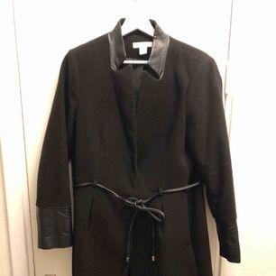 Svart kappa med skinndetaljer från H&M, sparsamt använd, köparen betalar ev frakt