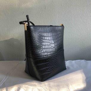 Svart väska med krokodilmönster. Använd en gång! Lite av en bucketstil på väskan. Säljer till högsta bud:)