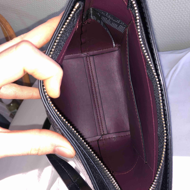 Svart väska med krokodilmönster. Använd en gång! Lite av en bucketstil på väskan. Säljer till högsta bud:). Väskor.