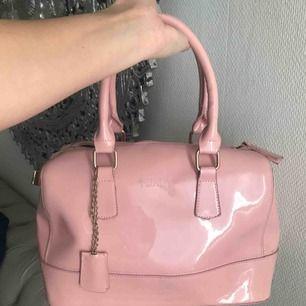 Supersöt rosa väska av märket Furla (ej äkta). Har bläck fläckar därav det låga priset. Fin och rymmer mycket. Frakt ingår i priset. Kan mötas upp i Stockholm (billigare då).