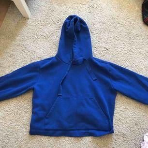 Kornblå hoodie, enbart använd 1 gång. Tröjan har breda ärmar och en lite kortare modell i magen (absolut inte magtröja dock). Mycket skönt material på insidan och den perfekta luvan en hoodie ska ha enligt mig.