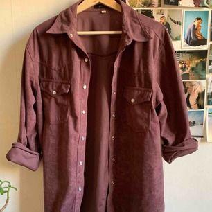 Jättesnygg skjorta i fakemocka! Lite cowboyfeeling på sömmarna. Lite mörkare och mer mättad lila i verkligheten