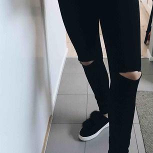 Stretchiga svarta jeans med hål på knäna.