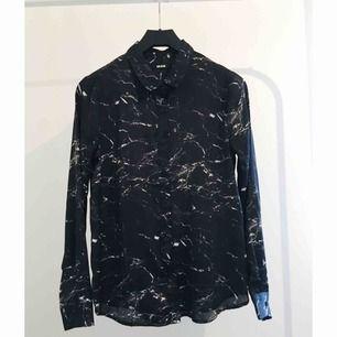 Svart marmorskjorta i glansigt material från Bikbok. Är i storlek XS men passar även S. Använd 1 gång.