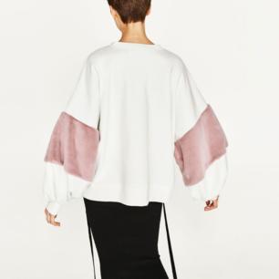 Sweatshirt med rosa faux fur på ärmarna. Ska sitta oversize!