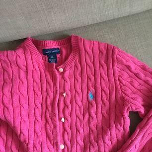 Ralph Lauren kabelstickad tröja/kofta med en volang, i rosa. Storleken passar folk med storlek Small. Jättebra skick, håller värmen bra! Självklart äkta.