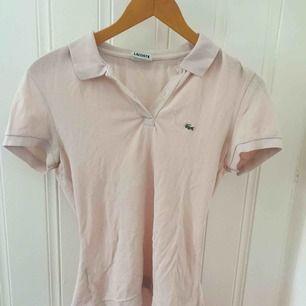 Ljusrosa pikétröja från Lacoste i storlek 38, dock passar tröjan bättre på en 34/36 beroende på hur man vill ha passformen. Använd en sommar