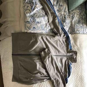 Grå träningsjacka med blå detaljer från Adidas säljes då den inte kommer till användning. Endast använd två gånger och köpt i USA. Tror det är herrstorlek S men snarare M för dam. Inkl. Frakt