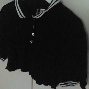 En svart pikétröja med ränder vid kragen och ärmarna. Aldrig använd, storlek M. :).