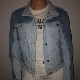 En ljusblå jeansjacka från Mango. Använd ett fåtal gånger och har en svag brun fläck på framsidan, annars i bra skick.