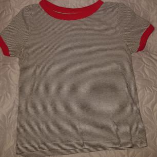 En svart vit randig tröja med röda ränderna runt hals och armar. Knappt använd. Strl XS, men lappen där storleken osv står är bortklippt. Frakt kan diskuteras senare 🌻 :)