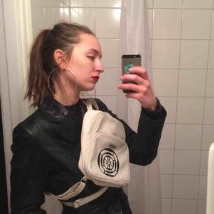 Liten vit vintage mini-ryggsäck med massa fack. I bra skick. Har klistrat på ett klistermärke på framsidan, tyckte den blev snyggare så men det är lätt att dra av om man inte vill ha kvar det. Gjord i vitt fuskskinn (vegan leather). Frakt 55 kr.