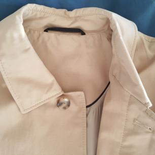 Trench coat, herr. Studio Mario Bigotti. Khaki med svarta detaljer och ljust foder. Två yttre fickor och två innerfickor med dragkedja. Storlek S/M, Längd 100 cm, axelbredd 50 cm, ärm 60 cm. Ny, oanvänd. Nypris ca 2.000 kr. Säljes 500 kr.