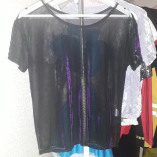 Säljer en mesh/transparant t-shirt med grön och lila touch. Använd 1 gång och bra kvalité. storlek M.  Fraktkostnad tillkommer vid frakt. Finns på Teleborg i Växjö, kan mötas i Växjö.