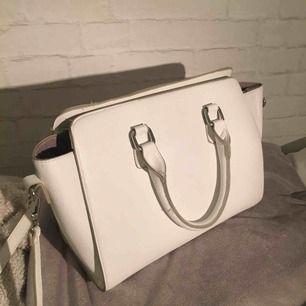 """Vit mellanstor handväska som har både små """"handtag"""" och en lång avtagbar axelrem! Väskan är väldigt rymlig och har små fack inuti!💞 Har använt väskan under ca 1 vecka så den är i väldigt fint skick! Kan mötas upp i Umeå annars står köpare för frakt!💋"""