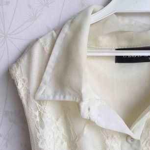 En jättefin sommrig klänning som nästa aldrig varit använd sitter jättefint på med spets på överdelen. Färgen är cremé eller en varmare beige färg. Som detaljer har klänningen även väldigt fina knappar