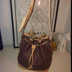 Dagmars Bucket Bag är en klassisk och slitstark väska med Dagmars klassiska print i canvas. Väskan har tre innerfickor. Den har en justerbar axelrem i läder samt dragsko för stängning. Material: Canvas print med läder detaljer. Mått: 34cm x 30cm x 21,5cm.