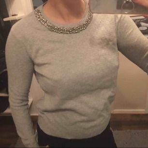 Mysig grå tröja med strass detaljer vid halsen  Använd fåtal gånger   Skickas mot frakt