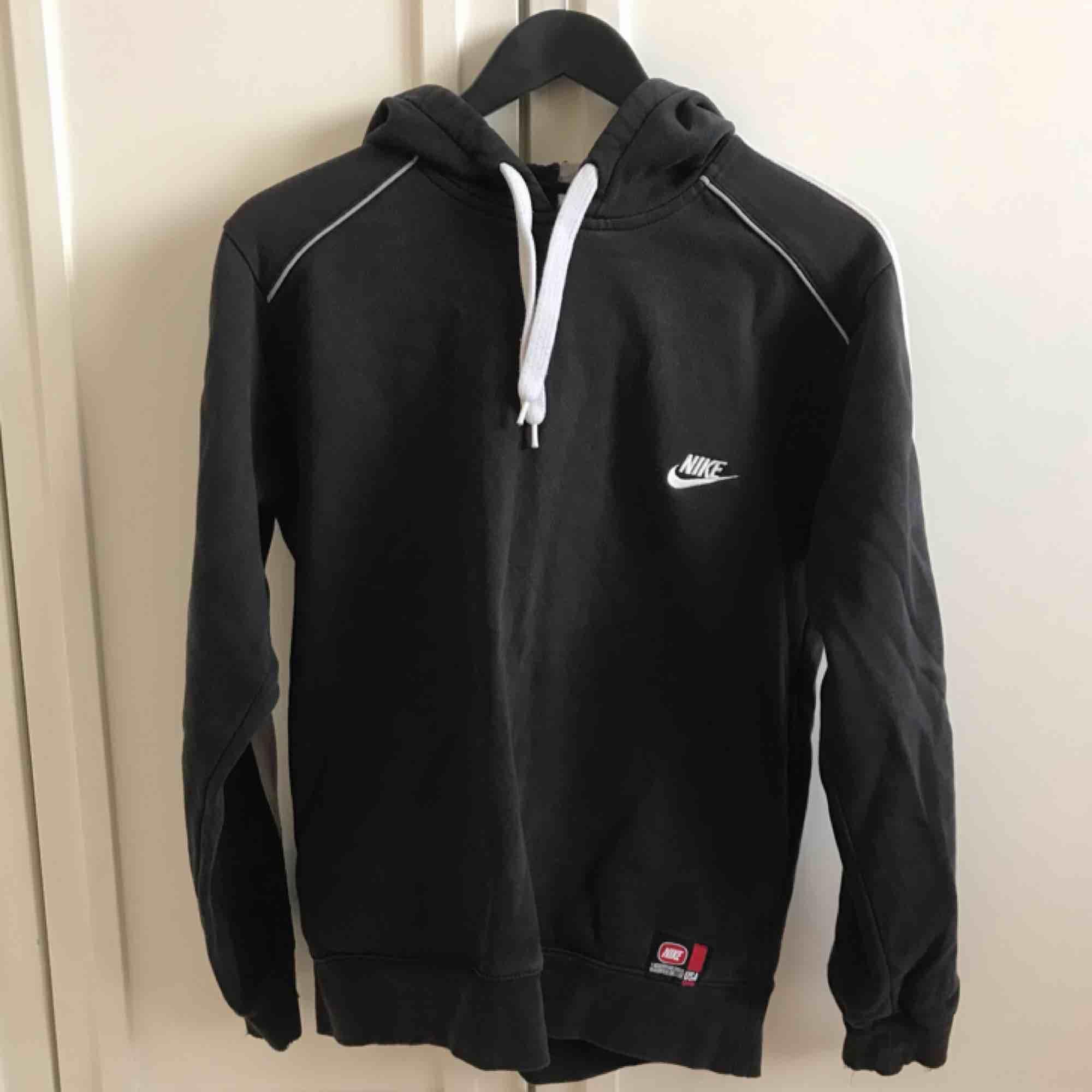 Vintage Nike hoodie i storlek S. Vit rand på ärmarna och luvan (helsvart på ryggen.) Har två fickor där fram!. Huvtröjor & Träningströjor.