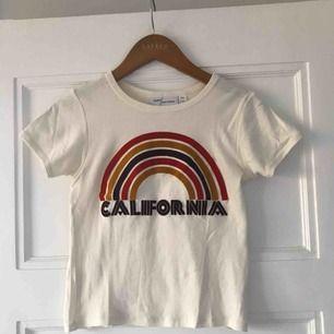 T-shirt från Urban Outfitters! Cremevit, lite kortare modell och med snyggt tryck. Är i nyskick! Frakten ingår🌸🌸🌸