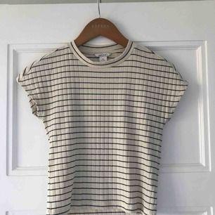 Supersöt cremevit t-shirt med mörkblå ränder från Monki! Croppad modell med lite högre hals! Är stretchig så passar även storlek S🥰 Frakten ingår