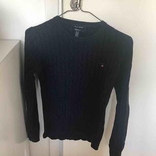 GANT kabelstickad tröja. Använd fåtal gånger därav är den i fint skick. Mörk marinblå i färgen.
