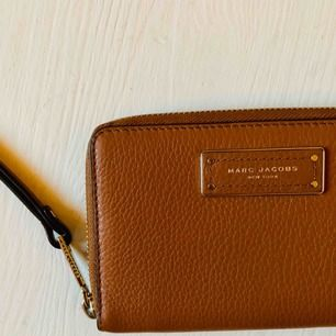 Ljusbrun wristlet plånbok från Marc Jacobs.  iPhone 8 får plats i mobil facket. Använd 2 gånger.