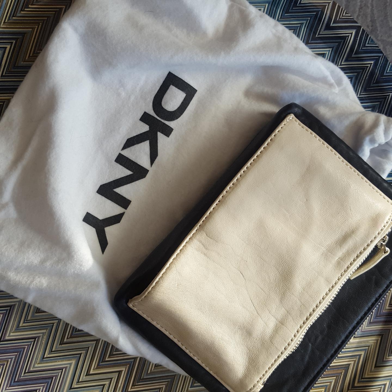 Svart/vit läder clutch från DKNY, lite slitage.  Köparen står för frakt  Betalning via swish . Accessoarer.