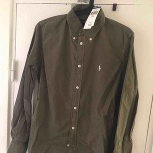 Säljer min aldrig använda skjorta från Ralph Lauren, storlek M. Skjortan är militärgrön. Köpare står för frakt