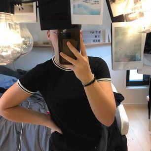 En svart t-shirt från Newyorker med svart vita randiga kanter, storlek xs.