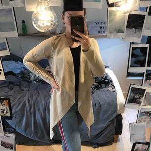 En beige nly trend coat/kappa med snöre vid ryggen från Nelly.com. Använd ett fåtal gånger och är i bra skick!