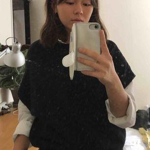 Stickad svart T-shirt. Snygg att ha över skjortan! 20% ull.