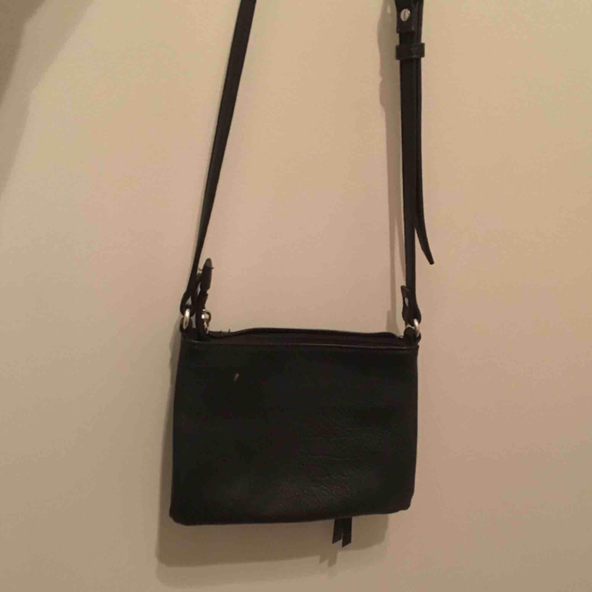 En svart liten handväska från Åhléns. På framsidan har den två fack med dragkedjor och i självaste väskan finns det två innerfack varav en har dragkedja.  Vi möts gärna upp i Stockholm men om frakt betalar köparen det. Väskor.