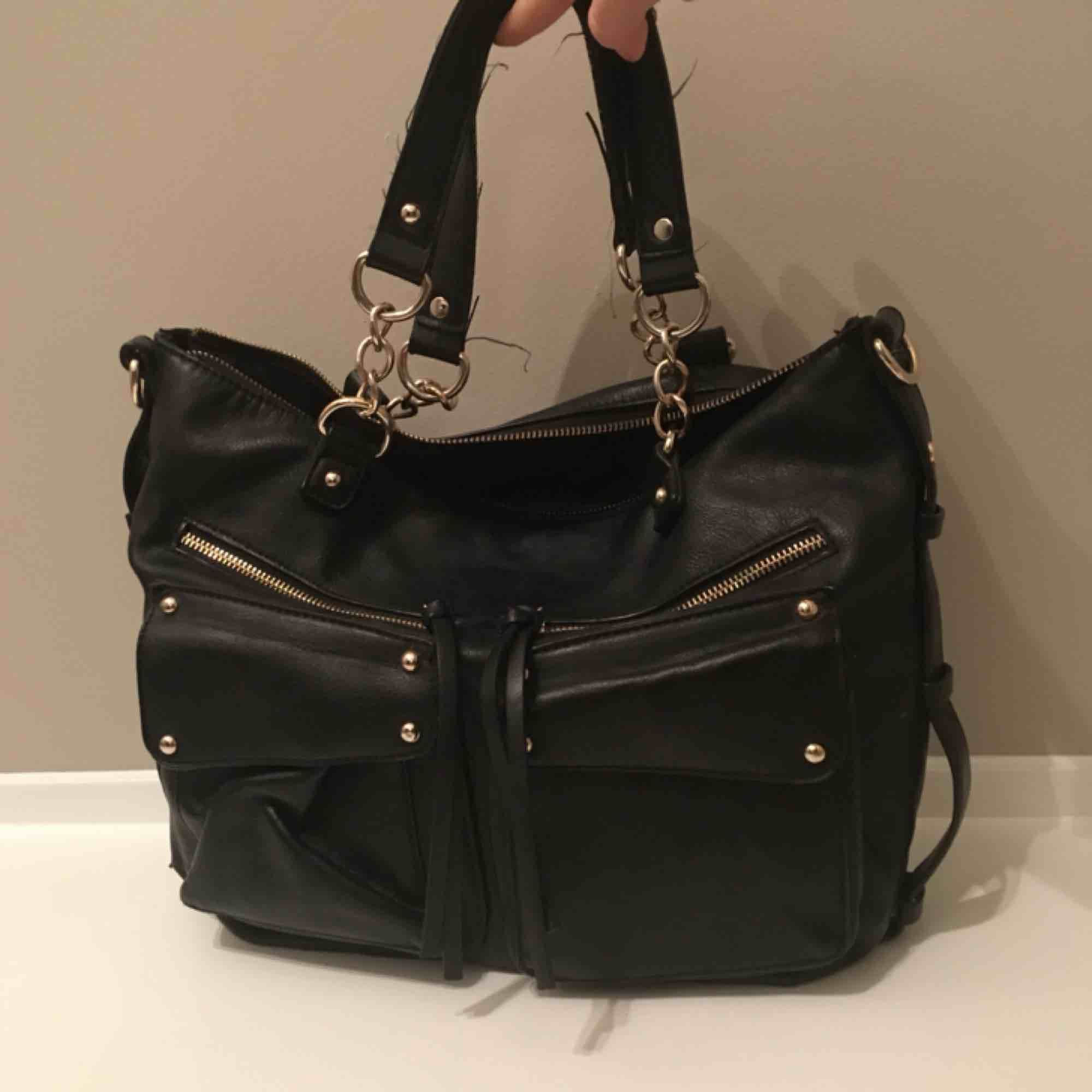 En svart väska med gulddetaljer. Den har väldigt många fack och funkar perfekt som skolväska! Vi möts gärna upp i Stockholm men om frakt betalar köparen det. Väskor.