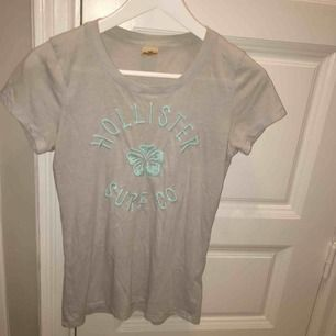 En ljusgrå t-shirt med ljusblå text från Hollister. Vi möts gärna upp i Stockholm men om frakt betalar köparen det