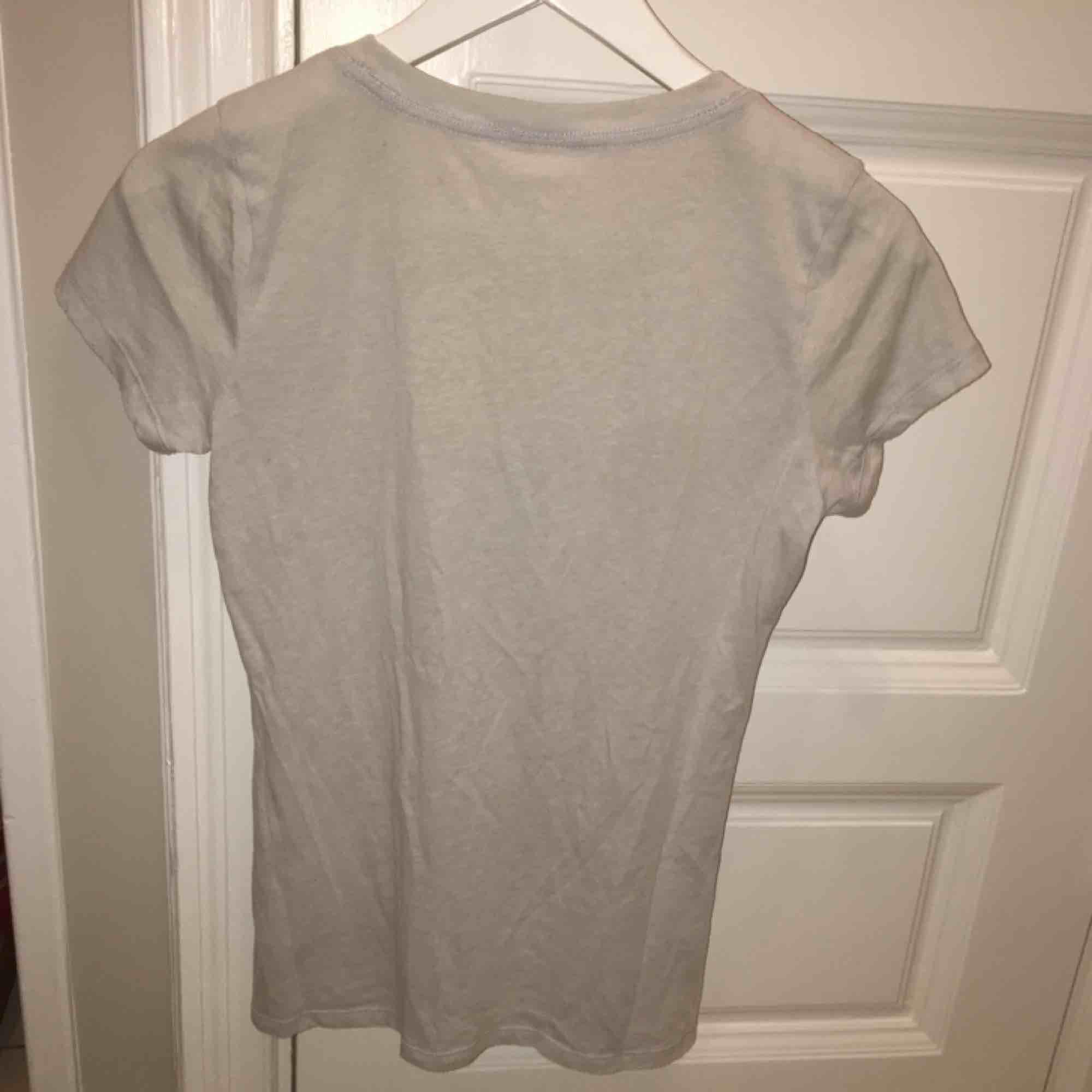 En ljusgrå t-shirt med ljusblå text från Hollister. Vi möts gärna upp i Stockholm men om frakt betalar köparen det . T-shirts.