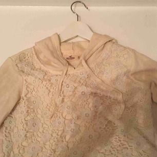En krämvit kort hoodie från Hollister. Jag har tagit bild både med och utan blixt. Vi möts gärna upp i Stockholm men om frakt betalar köparen det